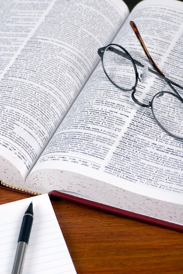 Dictionary and notebook 2. An open dictionary with a pair of glasses laying on top. A notebook and pen are sitting on the desk beside it royalty free stock images