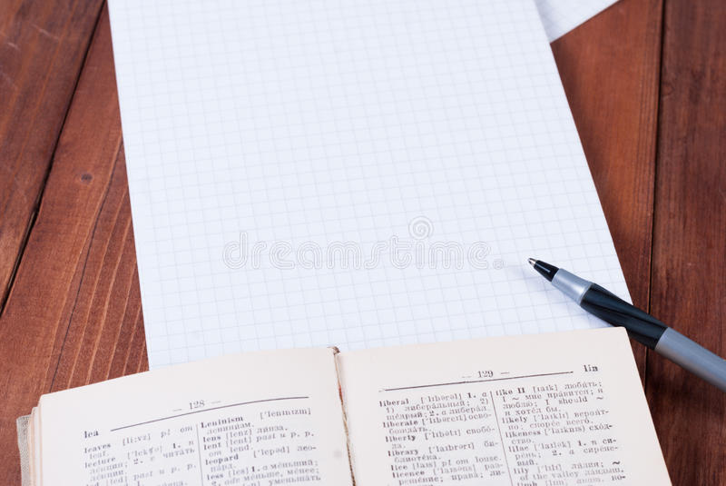 The dictionary, notebook and pen on a wooden surface. Lying on a wooden table dictionary, pen and notebook stock image