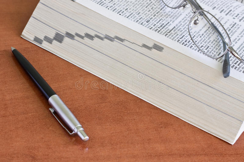 Dictionary with a pair of glasses and pen royalty free stock image