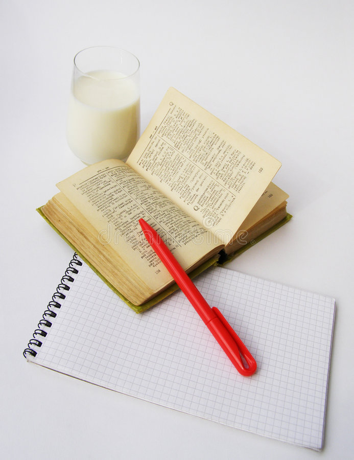 Dictionary and red pen. Notebook, the dictionary, the red pen and glass with milk on a white background stock photos