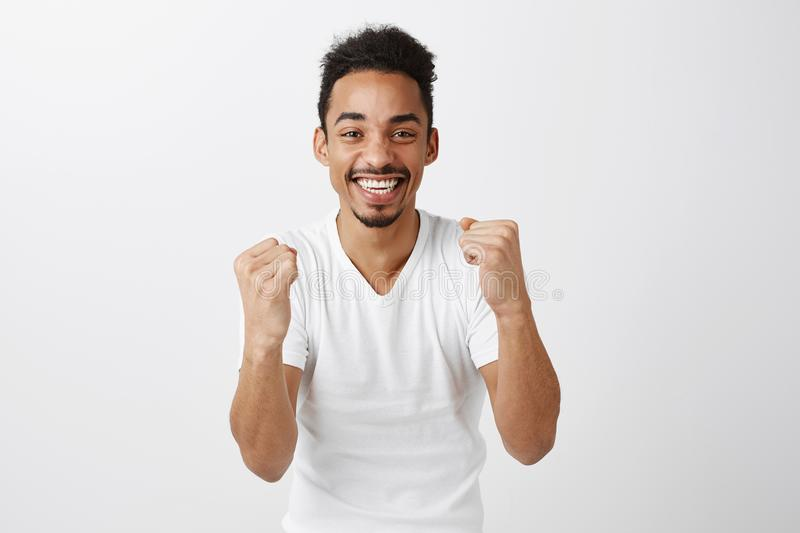 We did it together. Studio portrait of cheerful excited young male model with afro hairstyle raising clenched fists and stock photography