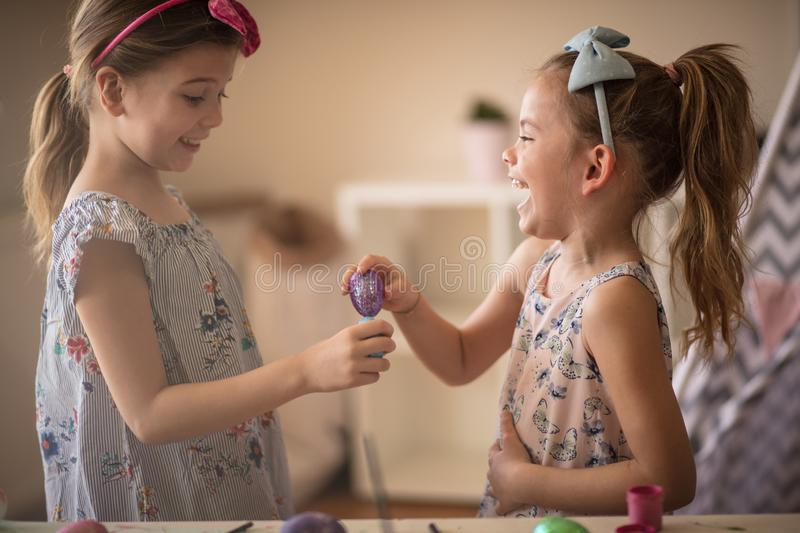 Did you get scared of losing it. ? Little girls having competition with Easter eggs stock images