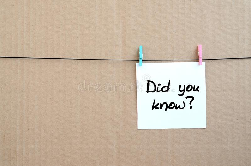 Did you know? Note is written on a white sticker that hangs with. A clothespin on a rope on a background of brown cardboard royalty free stock photography