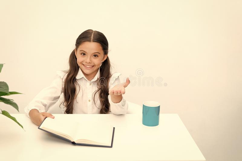 Did you know it. Reading textbook. Girl child reads book while sit table white background. Schoolgirl studying reading. Book. Kid girl school uniform happy face royalty free stock image