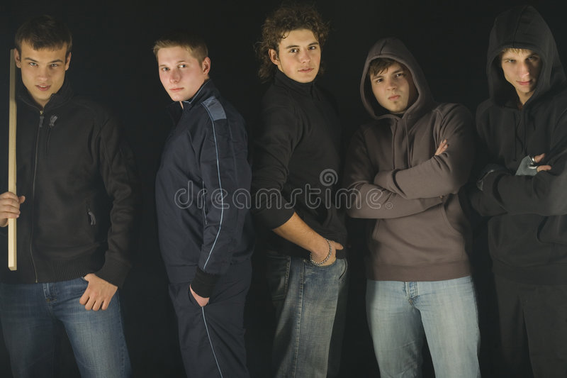Did you say something?. Group of angry hooligans. They are looking at camera and standing in dark place. Front view royalty free stock images