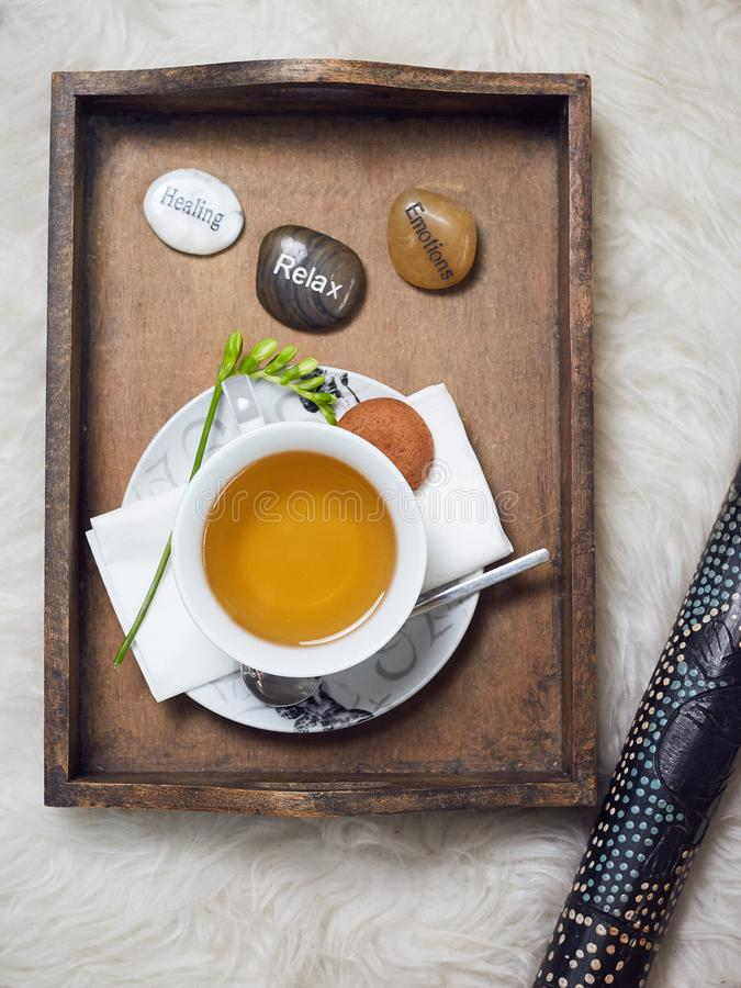 A didgeridoo and a wooden tablet with a filled teacup on it. Decorated with a flower and three labeled pebbles, Healing, Relax, stock photos