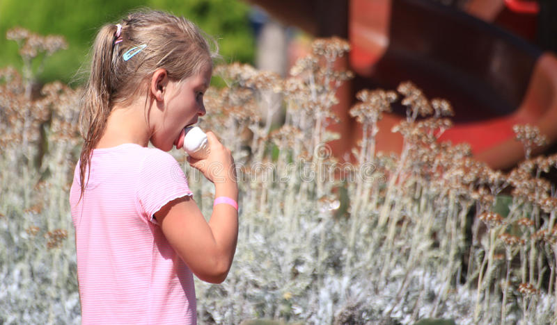 DIDIM, TURKEY - JULY 9, 2014. Casual portrait of a cute girl with an ice cream cone.  royalty free stock photo
