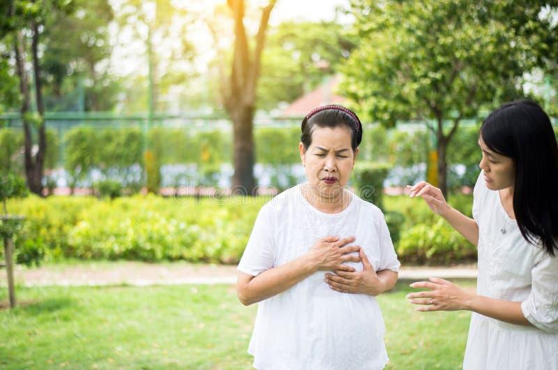 Die ältere asiatische Frau, die Schmerz- in der Brustleiden vom Herzinfarkt hat, Tochter mach's gut und Unterstützung stockbilder