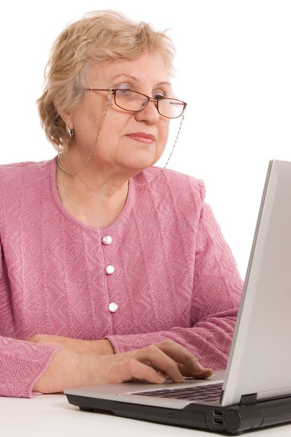 Die ältere Frau am Computer stockfotografie