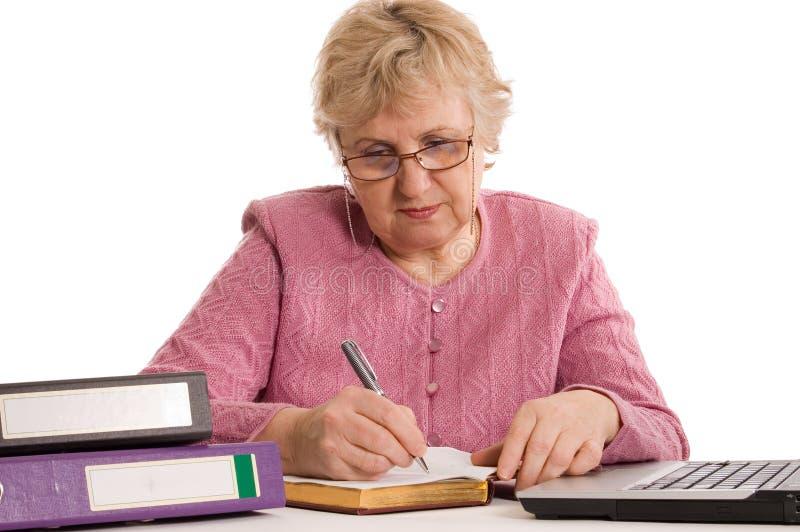 Die ältere Frau am Computer stockbild
