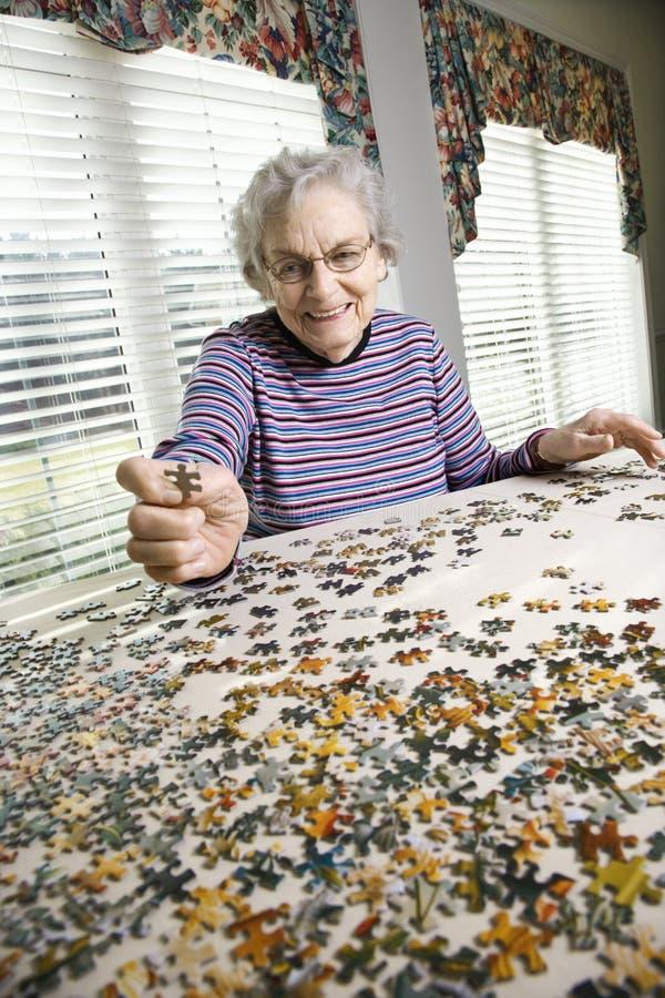 Die ältere Frau, die Spannvorrichtung tut, sah Puzzlespiel lizenzfreie stockfotografie