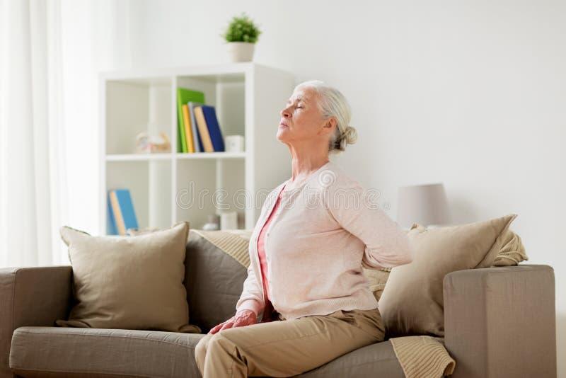 Die ältere Frau, die unter den Schmerz unterstützen leidet herein, zu Hause stockfotografie