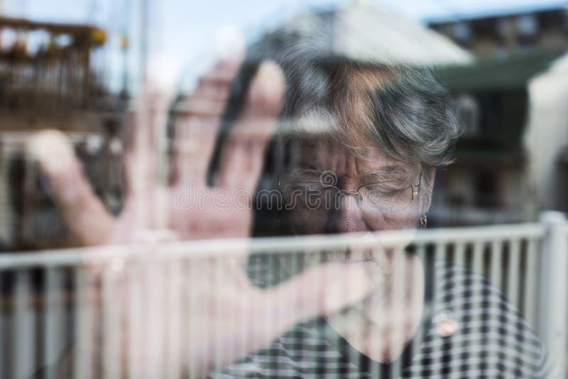 Die ältere Frau, die heraus durch ein Fenster wie schaut, drücken nieder stockbild