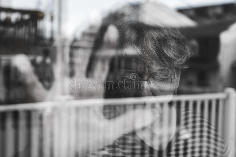 Die ältere Frau, die heraus durch ein Fenster wie schaut, drücken nieder stockfotos