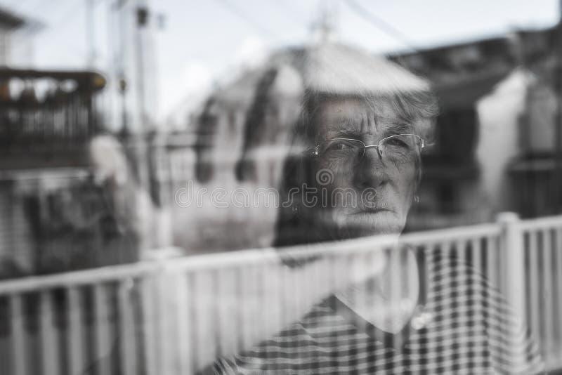 Die ältere Frau, die heraus durch ein Fenster wie schaut, drücken nieder stockbilder