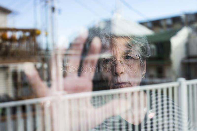Die ältere Frau, die heraus durch ein Fenster wie schaut, drücken nieder stockfotografie