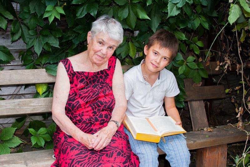 Die ältere Frau mit dem Großenkel las das Buch lizenzfreies stockfoto