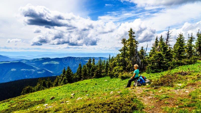 Die ältere Frau, die während einer Wanderung auf Tod Mountain nahe dem alpinen Dorf von Sun stillsteht, ragt in das Shuswap-Hochl lizenzfreie stockfotografie