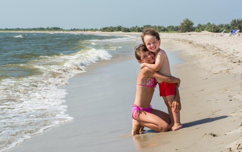 Die ältere Schwester umarmt ihren jüngeren Bruder auf dem Strand mit Wellen und Gischt, glückliche Kinder stockfotografie