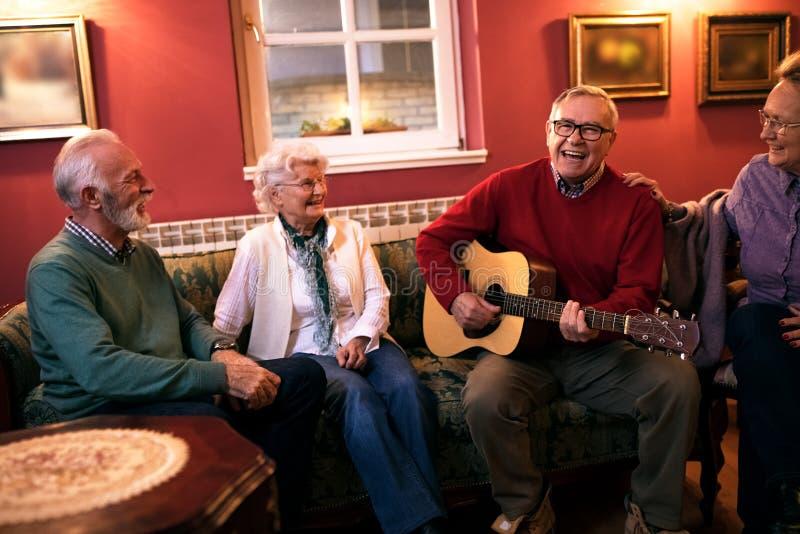 Die älteren Leute, welche die lächelnde Partei machen und genießen zusammen zu Hause lizenzfreies stockfoto