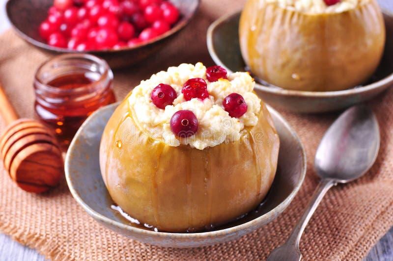 Die Äpfel, die mit Käse und Moosbeeren gebacken wurden, gossen Honig Gesundes Frühstück stockbild