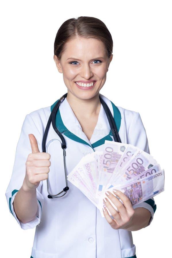 Die Ärztin, die Geld hält und Daumen lokalisierte zeigt oben, auf weißem Hintergrund lizenzfreie stockfotografie