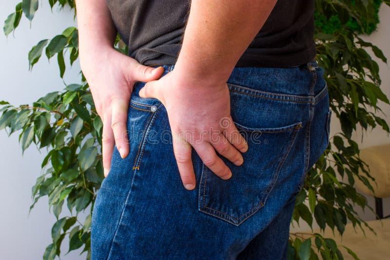 Die Äusserung von Schmerz im Hüftgelenkkonzeptfoto Der Mann seinen oberen Schenkel in dem das Hüftgelenk wegen plötzlicher Schmer lizenzfreie stockbilder
