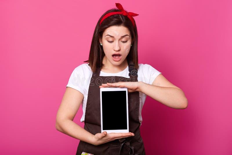 Die überraschte junge Frau, die digitale Tablette mit leerem Bildschirm hält, schaut unten, hält Mund geöffnet, hat erstaunt Gesi stockfotografie
