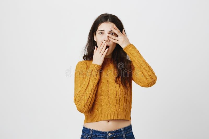 Die überraschte und intrigierte kaukasische Frau, die Bedeckung hält, öffnete Mund und Auge mit den Händen und spähte durch die F stockbilder