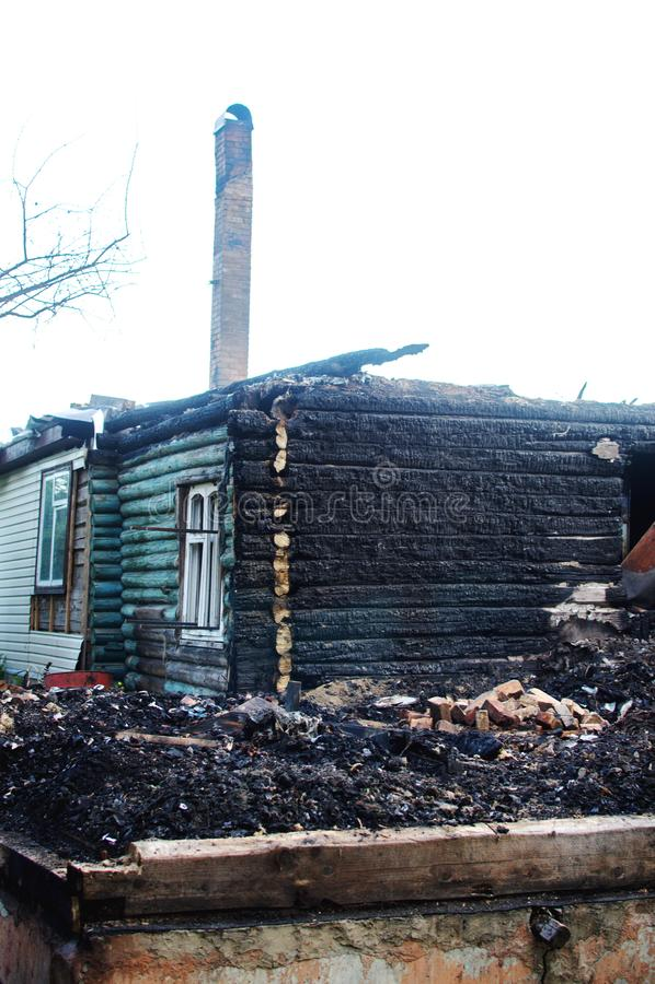 Die Überreste des Holzhauses nach dem Feuer stockbild