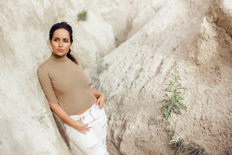 Die überzeugte elegante Frau, die auf dem Stein, tragend in der stilvollen Kleidung sich lehnt, wirft in der Natur auf, lokalisie lizenzfreie stockfotografie