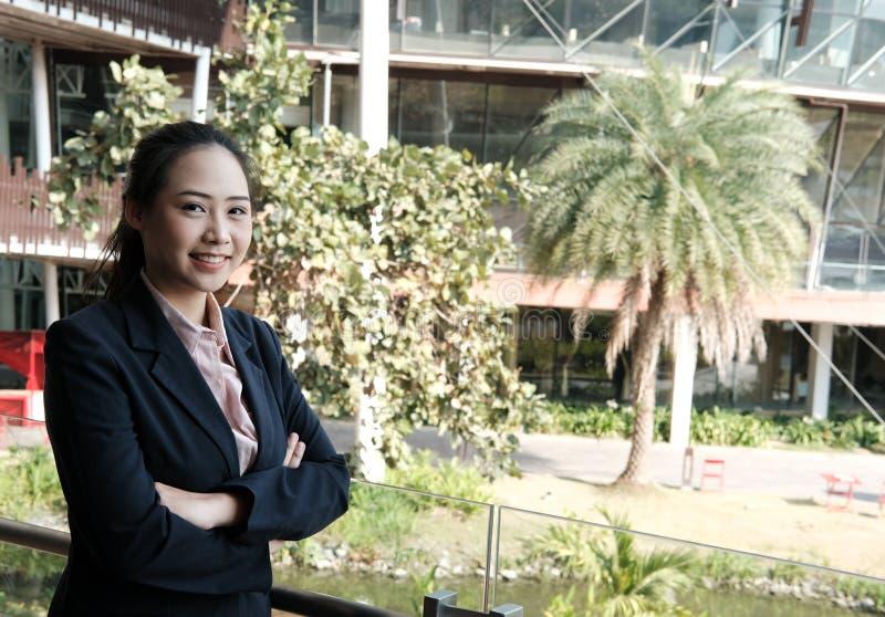 Die überzeugte Geschäftsfrau, die mit den Armen steht, kreuzte die offic Außenseite lizenzfreie stockfotografie