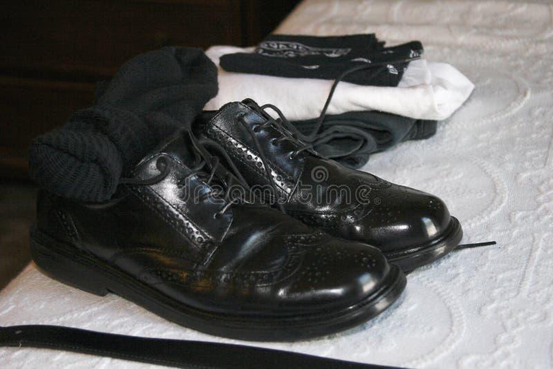 Die Abendschuhe der schwarzen ledernen Flügelspitzenmänner mit schwarzen Socken und Gurt stockbild