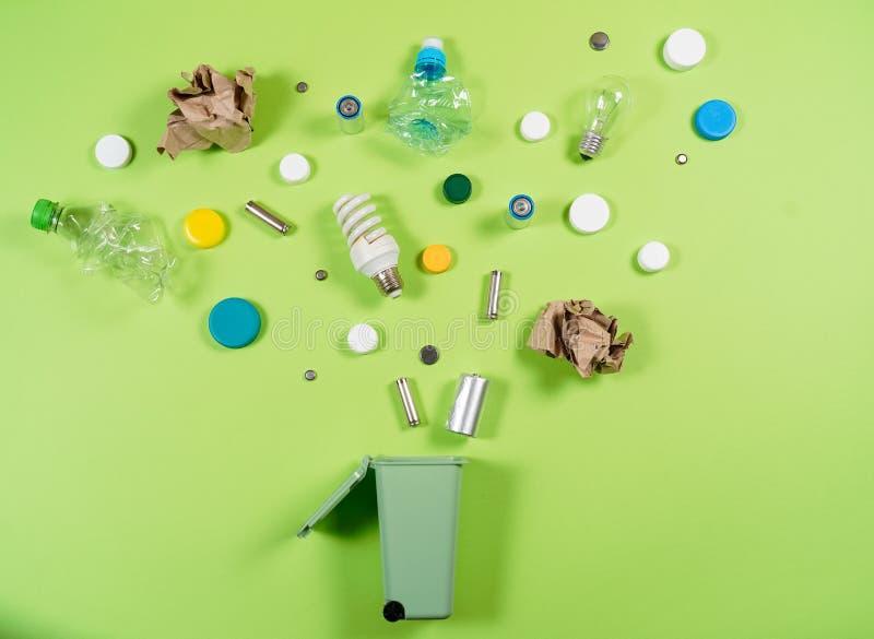 Die Abfalleimer und sortierter Abfall, die auf Grün lokalisiert werden, bereiten conce auf stockfotografie