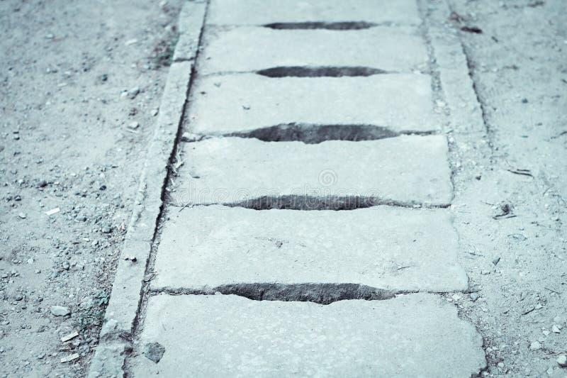 Die Abflussabdeckung wird vom alten, verfallenen Zement mit einem Sprung hergestellt und sollte verbessert werden lizenzfreie stockfotografie