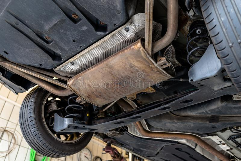 Die Abgasanlage im Auto, das von unterhalb, das Auto gesehen wird, ist auf dem Aufzug in der Autowerkstatt lizenzfreie stockbilder