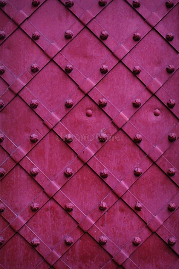 Die abgebrochene Beschaffenheit asphaltiert dunkelrote Farbe der Türen lizenzfreies stockfoto