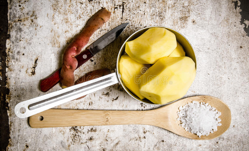 Die abgezogenen Kartoffeln in einer Metallkasserolle mit einem Löffelvoll Salz auf dem rustikalen Hintergrund stockfoto