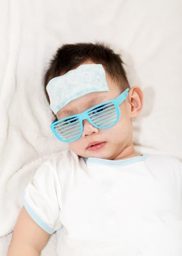 Die abkühlende Gelauflage der Kinderbefestigungs auf seiner Stirn stockfotografie