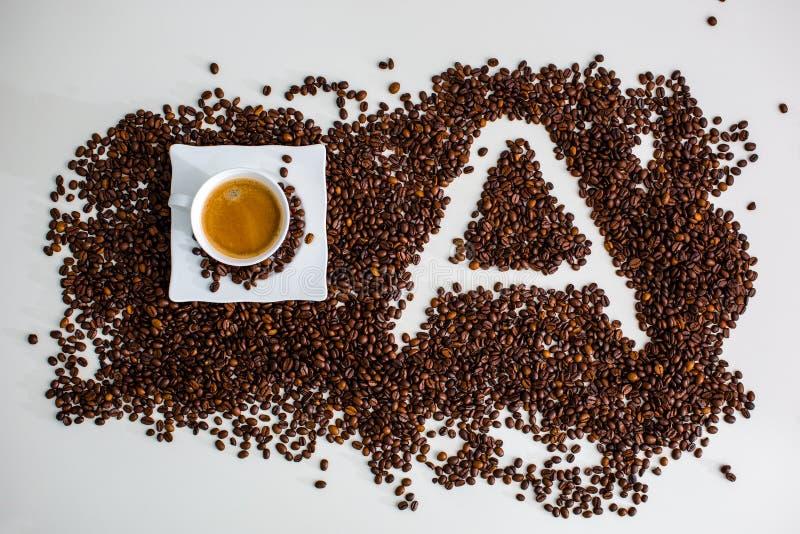 Die Ablagerungen sind der lokalisierte gebraute Kaffeebohne Schalenkaffee und das Bild des Buchstaben A lizenzfreie stockfotografie