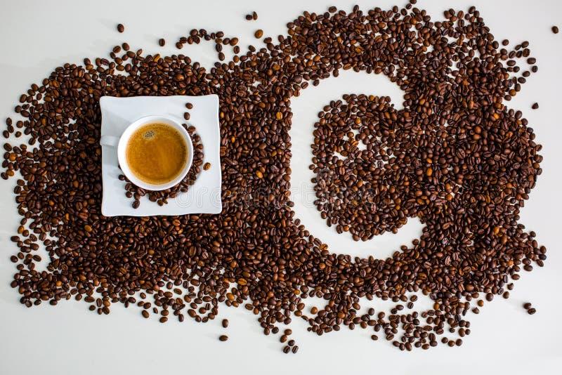 Die Ablagerungen sind der lokalisierte gebraute Kaffeebohne Schalenkaffee und das Bild des Buchstaben C stockbild