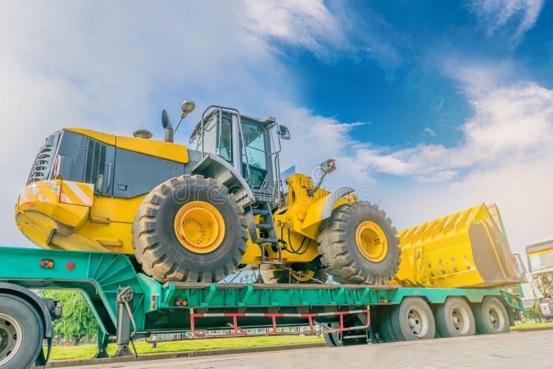 Die abstrakte Weichzeichnung des großen Traktors auf dem Abschleppwagen mit dem schönen Himmel und der Wolke, durch den Strahl, d lizenzfreie stockfotografie
