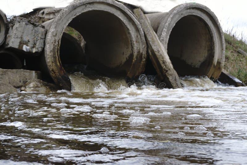 Die Abwasserwasserströme durch das alte Rohr lizenzfreies stockfoto