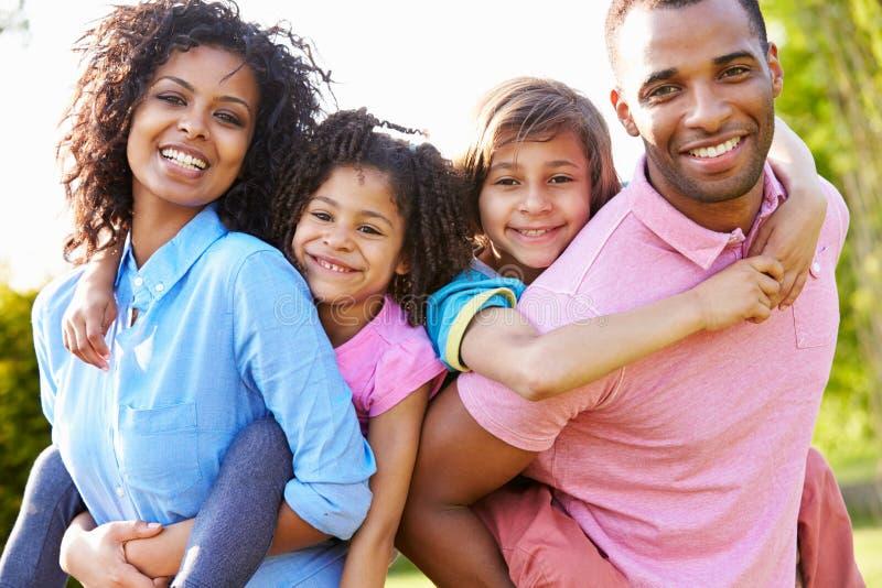 Die Afroamerikaner-Eltern, die Kinder geben, tragen Fahrten huckepack stockfotografie