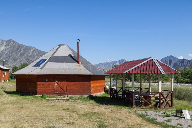Die alte Antike schmerzen Haus vom Holz ist rund-förmig mit einem Kamin auf die Mitte, für die nomadische Eingeborenen herein lizenzfreie stockfotografie