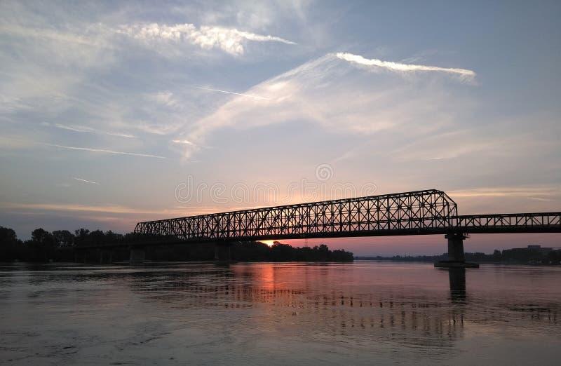 Die alte Eisenbahnbrücke auf dem Flusssonnenuntergang stockfotos