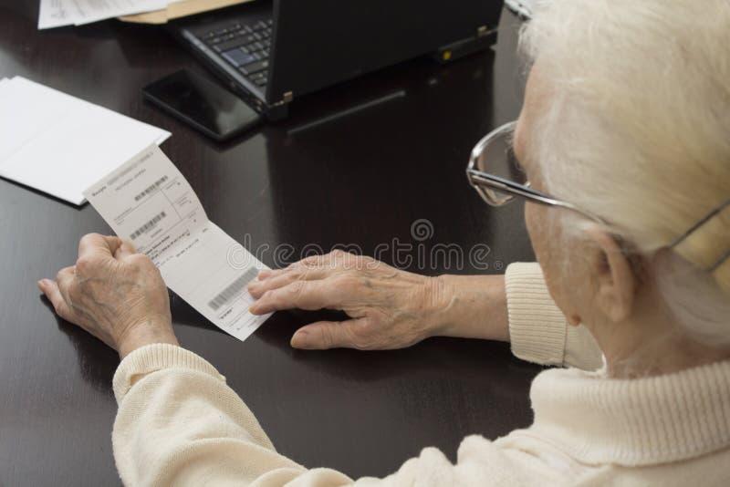 Die alte Frau hält in ihren Händen eine Verordnung und liest lizenzfreie stockfotos