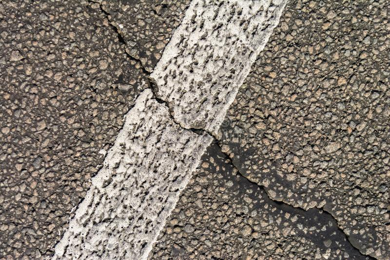 Die alte gebrochene Asphaltstraße Weiße Markierungen auf der Straße Reparieren Sie wird angefordert Kopieren Sie Platz lizenzfreie stockfotos