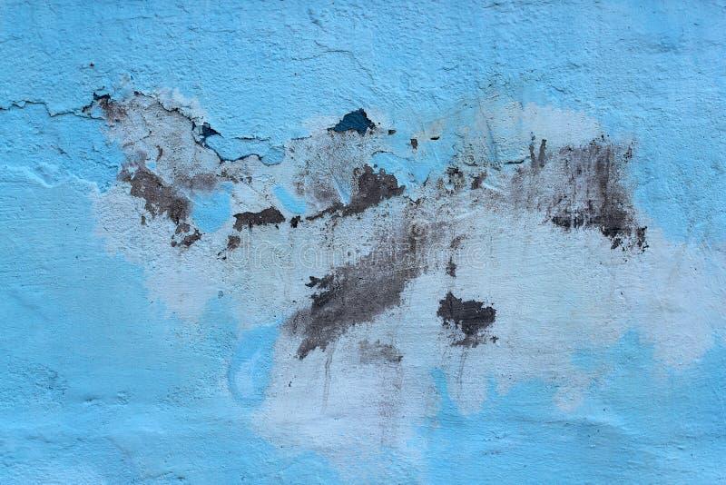 Die alte masern Sie Farbe, abgezogene weg Stücke von der Wand, blauer Hintergrund Konzeptsonnenstrahlung, Korrosion stockfotos