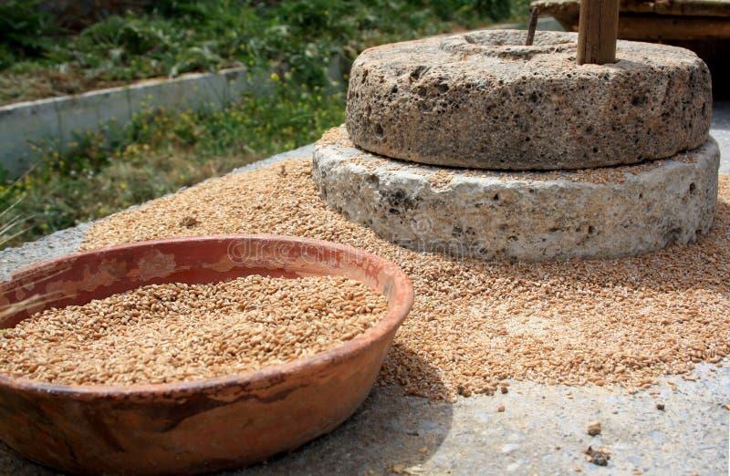 Die alte Quernstein-Handmühle mit einer Schüssel Korn stockbilder